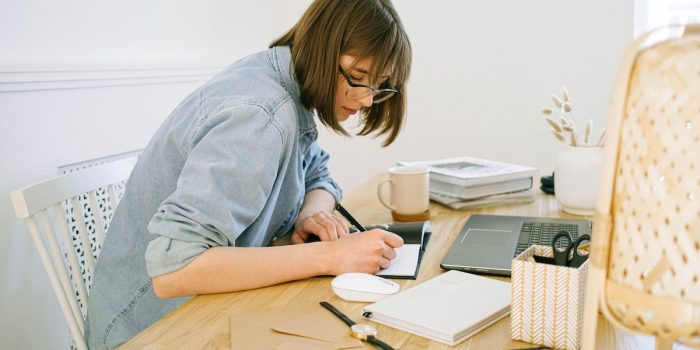 woman-writing-on-a-notebook-4240571